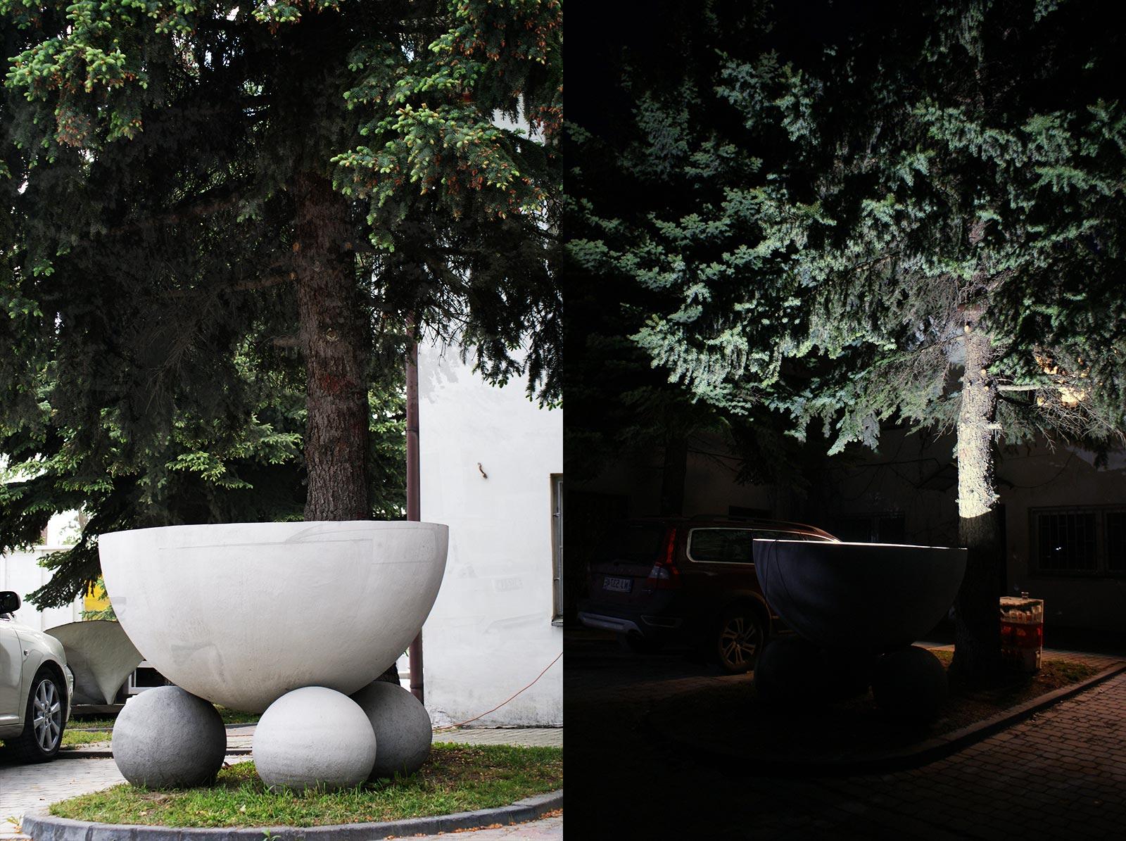 Duża lampa betonowa oświetlająca drzewa w ogrodziea