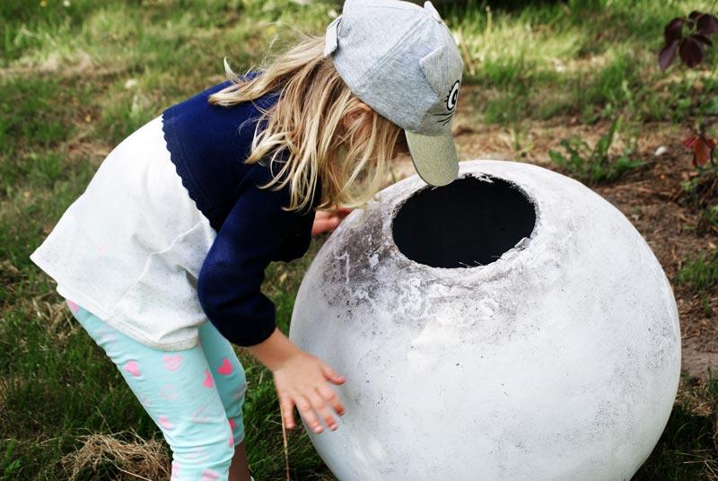 Dziewczynka zagląda do wnętrza pustej w środku kuli betonowej
