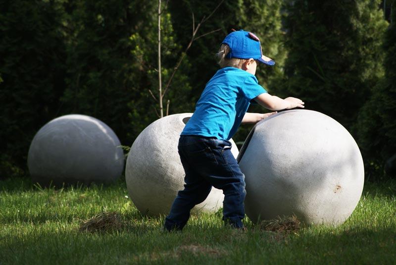Chłopiec przetaczający lekkie kule betonowe ogrodowe