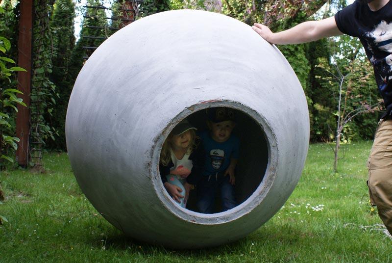 Dzieci we wnętrzu betonowej kuli ogrodowej