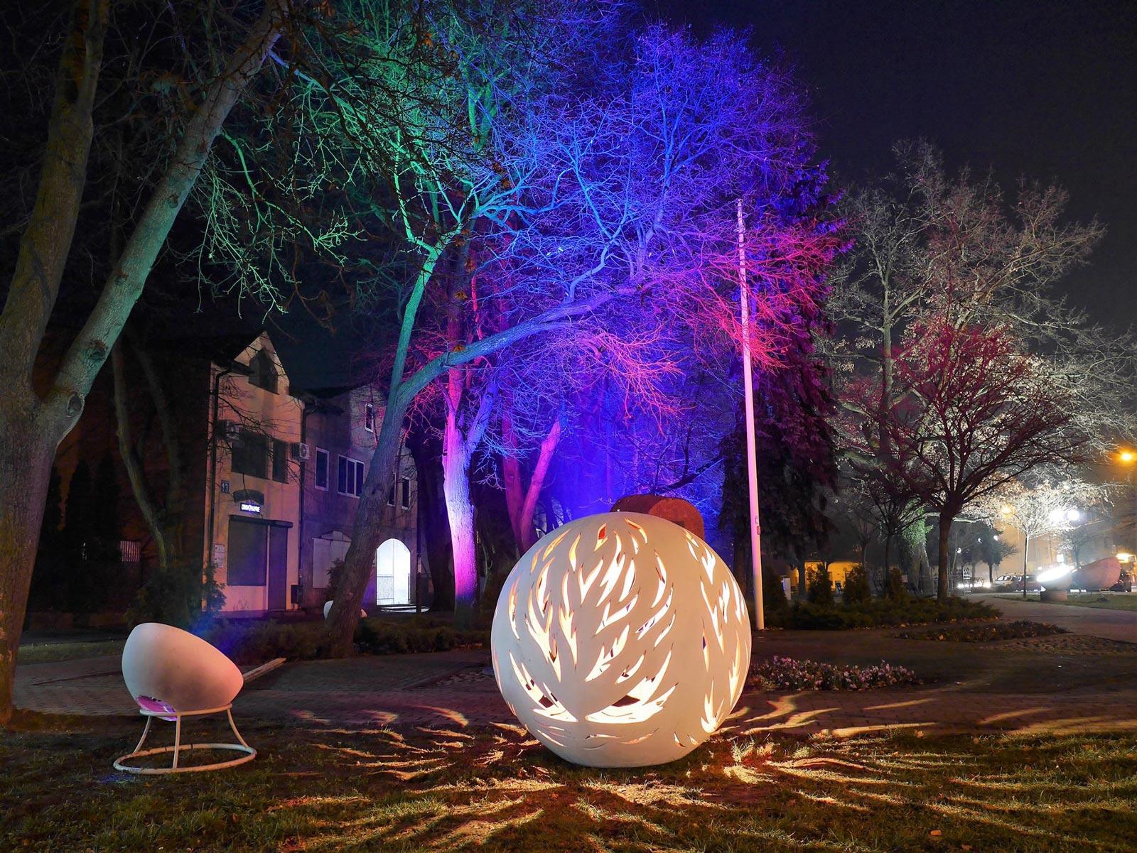 Park oświetlony kolorowym światłem ukrytym w betonowej kuli