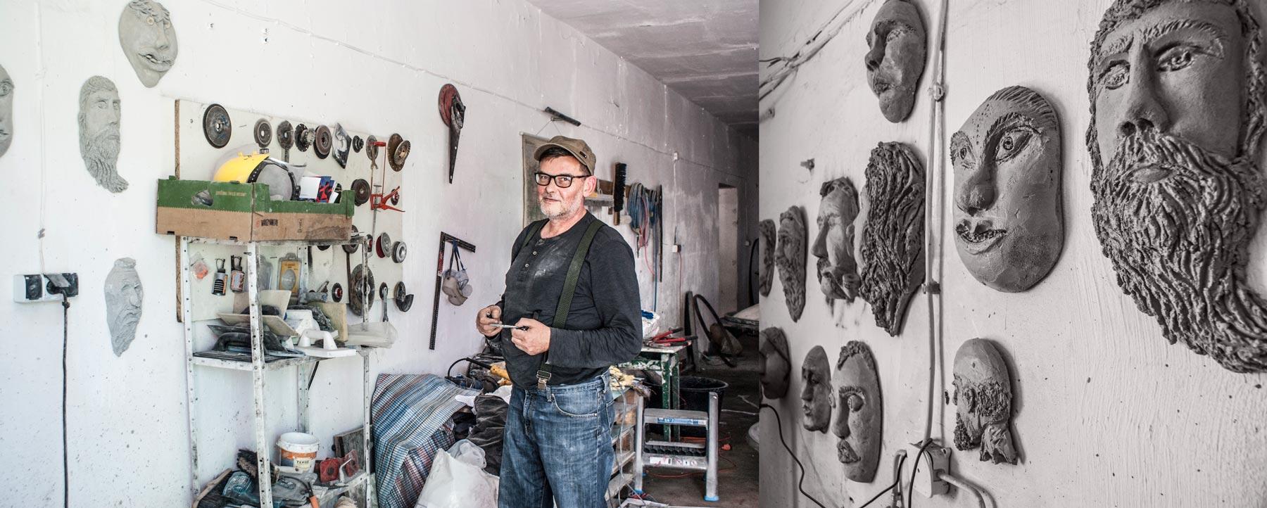 Robert Kowalski przy swoich betonowyh płaskorzeźbach