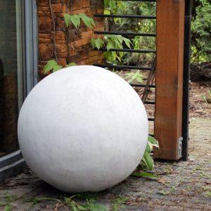 Kula betonowa gładka o naturalnym wyglądzie pusta w środku z lekkiego betonu ustawiona w altanie przy domu