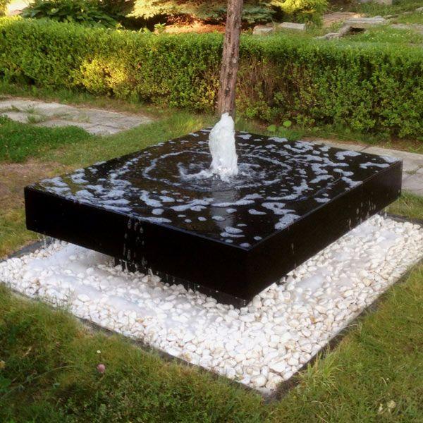 Fontanna betonowa o wyglądzie monolitycznego kamiennego bloku z czarnego granitu